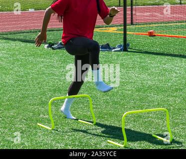 Ein High School weiblichen Leichtathlet ist darstellende Form Bohrer ohne Schuhe durch steping über Gelb mini Hürden auf grünem Rasen. - Stockfoto