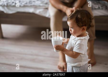 Kleine niedliche Mädchen mit einer Schale Fuß zu Hause. Mother's helper.Nahaufnahme, Seite, Ansicht Foto. lifestyle, Kindheit - Stockfoto