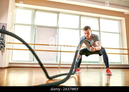 Junge Menschen aus und arbeiten mit Schlacht Seile an ein Fitnessstudio. - Stockfoto