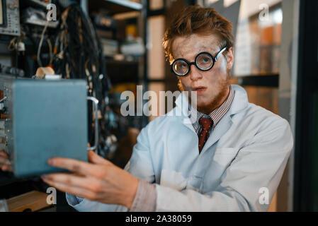 Wissenschaftler in Gläsern hält elektrisches Gerät - Stockfoto