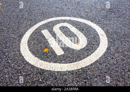 10 Meile pro Stunde Höchstgeschwindigkeit Zeichen in weiß auf Asphaltstraße Oberfläche lackiert - Stockfoto