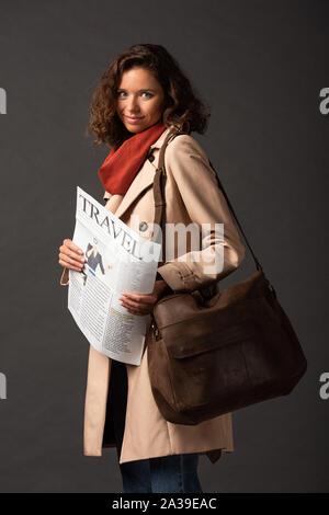 Lächelnde Frau in Trenchcoat mit Leder tasche Holding reisen Zeitung auf schwarzem Hintergrund - Stockfoto
