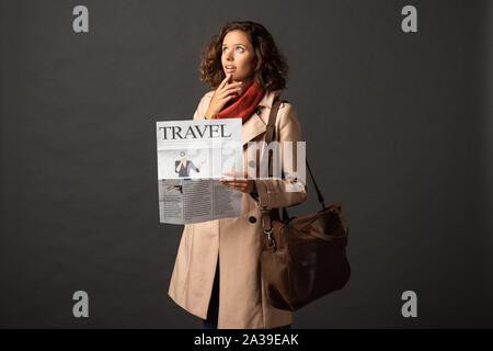 Nachdenkliche Frau in Trenchcoat mit Leder tasche Holding reisen Zeitung auf schwarzem Hintergrund - Stockfoto