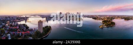 Große Sydney Wahrzeichen der Stadt am Ufer des Hafens von Sydney, die durch massive Stahl Bogen der Harbour Bridge verbunden zu den Felsen und CBD Barangaroo am sunri - Stockfoto