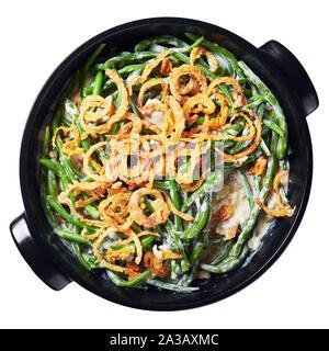Herrlich grünen Bohne Kasserolle bestreut mit knusprig gebratenen Zwiebeln in einem schwarzen Teller auf weißem Hintergrund, amerikanische Küche, Ansicht von oben, Fla - Stockfoto