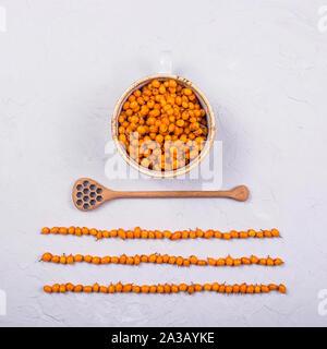 Helles orange Sanddorn Beeren in einer Schale, die neben einem Löffel Honig. Herbst wärmenden Tee Konzept. Ansicht von oben, flach - Stockfoto