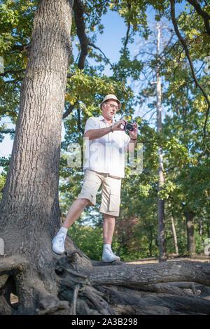Reifen Mann mit Hut holding Foto Kamera während der Aufnahme - Stockfoto