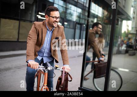 Happy Geschäftsmann Reiten Fahrrad in Morgen zu arbeiten - Stockfoto