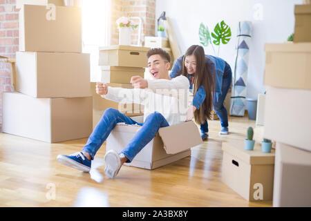 Lustige asiatischen Paar Spaß, Reiten im inneren Karton lächelte glücklich, sehr aufgeregt, Umzug in ein neues Haus - Stockfoto