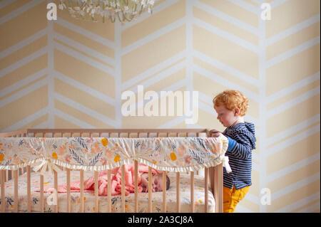 Toddler boy peeking in über Krippe Schiene bei neugeborenen Babys schlafen in der Krippe