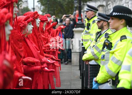 Die Demonstranten, betitelt der Roten Rebellen, außerhalb des Cabinet Office auf Whitehall, während ein Aussterben Rebellion (XR) Protest in Westminster, London.
