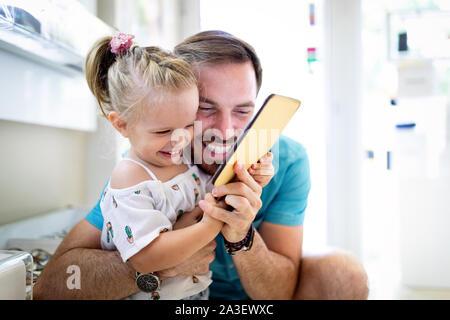 Glückliche freudige junge Vater mit seiner kleinen Tochter. Vater und Kind Spaß haben - Stockfoto