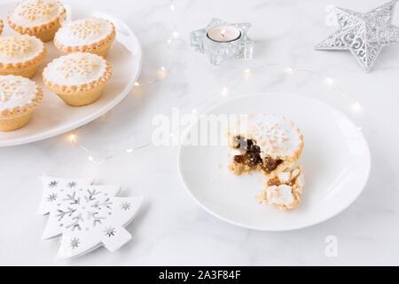 Mince Pies auf Platten, Weihnachtsdekoration, Teelicht und Lichterketten auf weißem Hintergrund. - Stockfoto