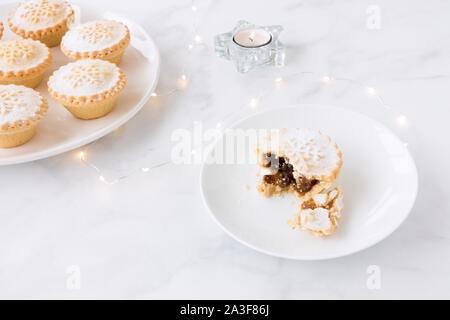 Mince Pies auf Platten mit Kerzen und Lichterketten auf weißem Hintergrund mit kopieren. - Stockfoto