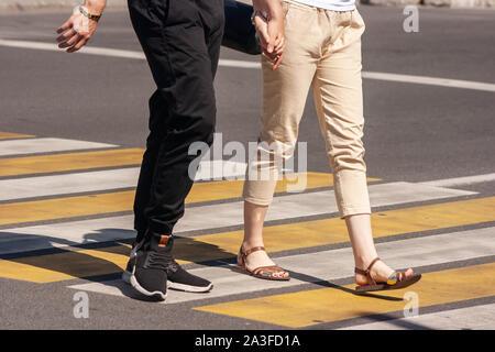 Beine der jungen Fußgänger auf dem Zebrastreifen in der Stadt im Sommer Tag - Stockfoto