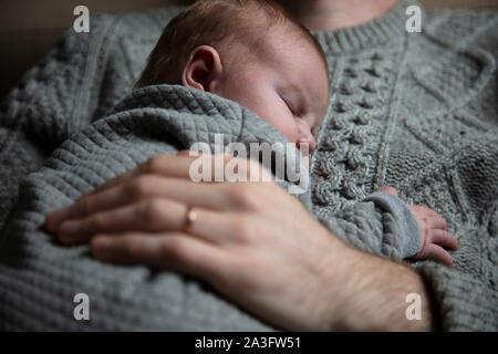 Ein Vater seinen Sohn auf seine Brust hält. Familie Abbinden. Vaterschaft