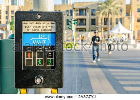 Fußgängerüberweg Schaltfläche Maschine in Arabisch und Englisch an der Kreuzung mit der Leute im Hintergrund - Stockfoto
