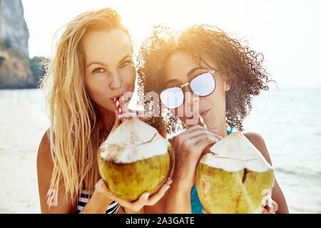 Lächelnde junge Frauen Bikinis tragen und Trinken von Kokosnüssen gemeinsam an einem tropischen Strand in den Sommerferien - Stockfoto