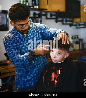 Ein big eyed Boy mit Schürze sitzt in Barbier Stuhl, während mit Haarschnitt in trendigen '81 Friseure shop in Tucson, AZ - Stockfoto