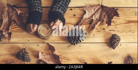 Frau Hände halten eine heiße Tasse Tee auf einem hölzernen Herbst Hintergrund mit Herbstlaub und Kiefer Kegel. Ansicht von oben. Wärmendes Getränk in kalten Herbst Tage - Stockfoto