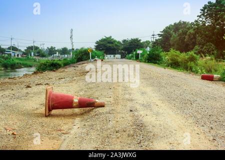 Die alte Leitkegel, die auf der Straße, die entlang der Bewässerungskanal für Landwirtschaft repariert wurde. - Stockfoto