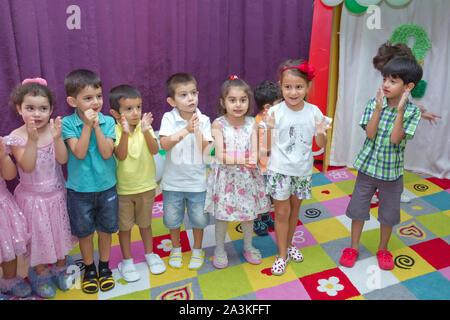 Geburtstag zwei Jahre in den Kindergarten. Kindergeburtstag mit Animatoren. Happy Gruppe von Kindern bei einer Geburtstagsfeier im Stil gekleidet - Stockfoto