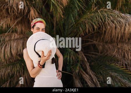 Junge Frau in einem weißen Kleid deckt seinen Mund mit Hut in der Nähe stehenden Baum zu Palm