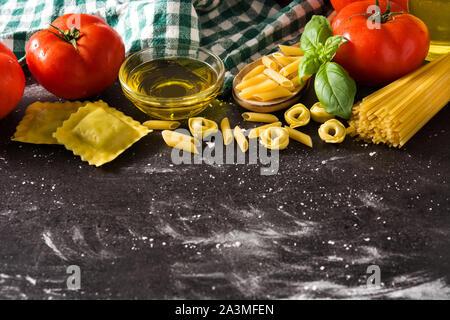 Italienische Pasta und Zutaten. Ravioli, Nudeln, Spaghetti, Tortellini, Tomaten und Basilikum - Stockfoto