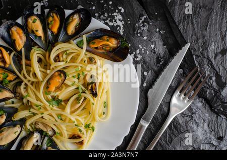Italienische Pasta Spaghetti mit Miesmuscheln und Petersilie auf dunklem Hintergrund. Leckeres Essen Konzept. - Stockfoto