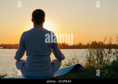 Ein junger Mann sitzt auf einem See bei Sonnenuntergang, Yoga. Sitzt in der Pose des ardhapadmasana, padmasana. Gleichgewicht, Harmonie, Balance, Konzentration, Entspannung. - Stockfoto