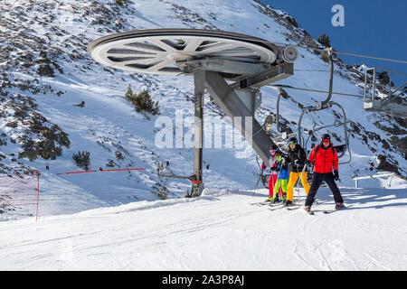Pyrenäen, ANDORRA - Februar 13, 2019: eine Gruppe von Skifahrern in bunten Kleidern gehen weg vom Sessellift an der Spitze. Schneebedeckten Hang und Metall Struktur - Stockfoto