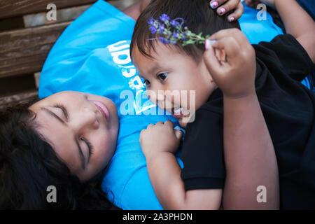 Einen kleinen Bruder, seine ältere Schwester eine Umarmung und der älteren Schwester, freundlich und liebevoll auf ihn zu, während die Festlegung in einer Bank. - Stockfoto