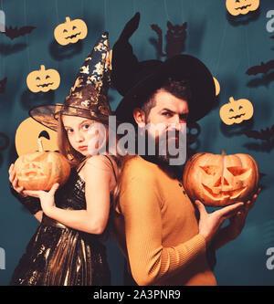Vater und Tochter in Kostümen. Halloween Party und Urlaub Konzept. Assistenten und kleine Hexe in schwarze Hüte halten Kürbisse. Mädchen und bärtiger Mann mit zuversichtlich Gesichter auf grünem Hintergrund grau mit Dekor - Stockfoto