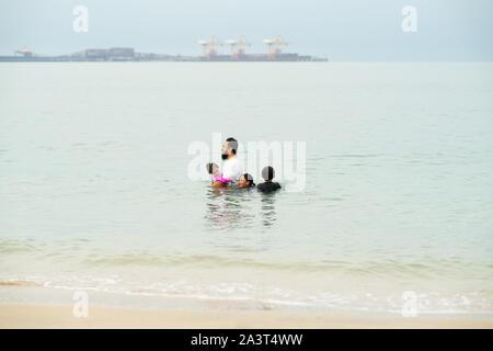 Gerne asiatische Familie mit Kind Spaß am Strand. Freudige Familie. Reisen und Ferien - Stockfoto
