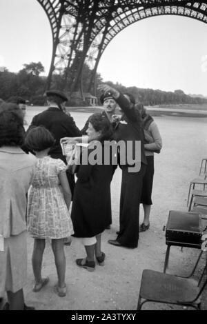 Touristengruppe vorm Eiffelturm, Paris, Frankereich, 1940er Jahre. Touristische Gruppe vor dem Eiffelturm, Paris, Frankreich, 1940er Jahre. - Stockfoto