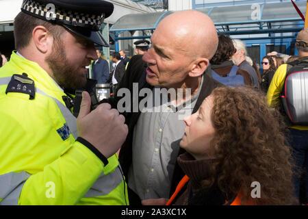 Umweltaktivisten argumentieren mit Polizisten, während über den Klimawandel während der Besetzung von City Flughafen (London's Business Travel Hub protestieren) im Osten Londons, der vierte Tag der zwei Wochen anhaltenden weltweiten Protest von Mitgliedern des Aussterbens Rebellion, am 10. Oktober 2019, in London, England. - Stockfoto