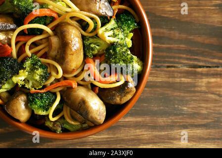Nahaufnahme von ei Nudeln mit Gemüse in der Schüssel. Warmes Essen im Wok in Ost Stil auf Holztisch. Ansicht von oben, flach - Stockfoto