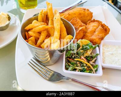 Fisch und Chips. Gebratener Fisch in Teig mit Chips, sauce, Gemüse serviert, und Ketchup - Stockfoto
