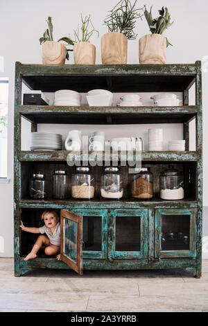 Junge versteckt sich im Schrank in der Küche - Stockfoto