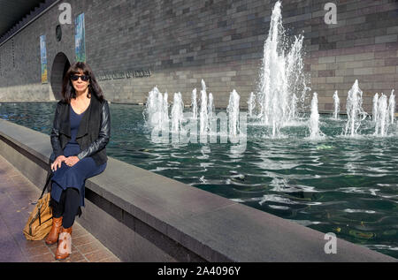 Frau sitzt auf der Kante eines Brunnen vor der Nationalgalerie von Victoria nach dem Besuch der Vincent Van Gogh Ausstellung. - Stockfoto