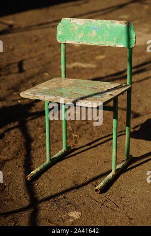 Alten grünen Stuhl im Hof auf dem Steinboden, hartes Licht und s - Stockfoto