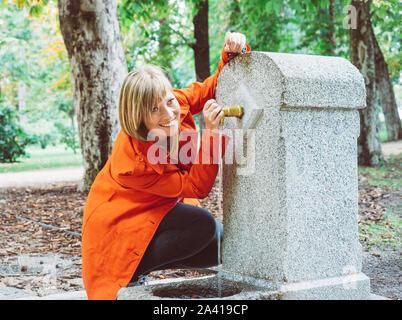 Kaukasische Mädchen mit roter gabardine Getränke Wasser aus einem Brunnen in einem Park in Madrid - Stockfoto