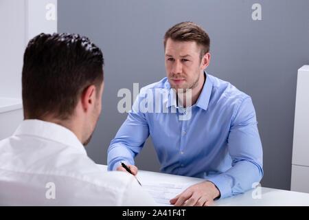 Portrait einer jungen Geschäftsmann in der Diskussion mit seinen Kollegen im Büro Treffen - Stockfoto