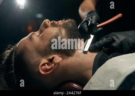 Nahaufnahme von Friseur Hände in schwarz Handschuhe, trendige Bart Form für Client mit scharfen Rasiermesser im barbershop. Konzept der professionellen männlichen Schönheit Behandlung - Stockfoto