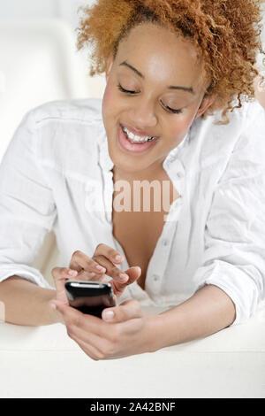Schöne junge Frau SMS auf ihr Handy an Freunde - Stockfoto