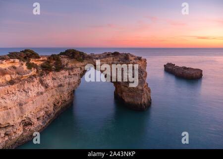 Algarve Strand bei Sonnenuntergang. Liebevolle Moment unter Natural Arch in Stein gemeißelt ist eine touristische Attraktion an der Südküste von Portugal. Panoramablick vom - Stockfoto