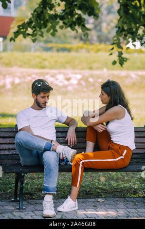 Junges Paar sitzt auf der bank Streit mit einander im Park - Stockfoto