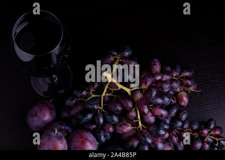 Frische blaue Pflaumen, Weintrauben und Glas Wein auf einem schwarzen reflektierenden Hintergrund - Stockfoto