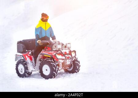 Ein Mann reitet viel Schnee auf einem ATV im Winter, Hintergrund, quadracycle, kopieren Raumfahrt, Verkehr - Stockfoto