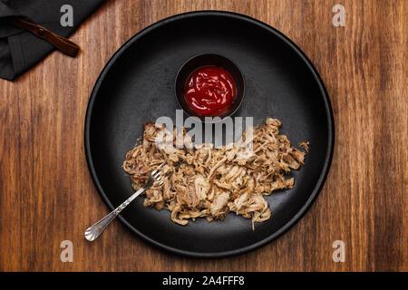 Zog Schweinefleisch in einer schwarzen Platte auf einem Holztisch - Stockfoto